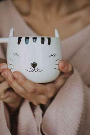 person holding white cat mug